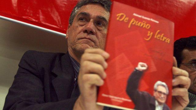 Alfredo Crespo con un libro de Abimael Guzmán
