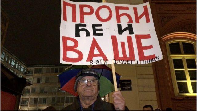 """Penzioner sa transparentnom na kome piše """"Proći će i vaše, vrati oduzete penzinje"""""""