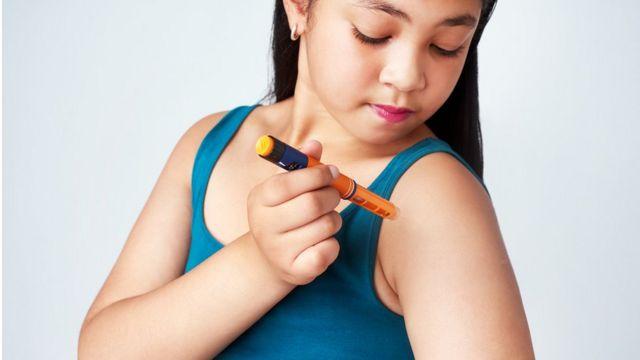 Imagem mostra menina injetando insulina no próprio braço