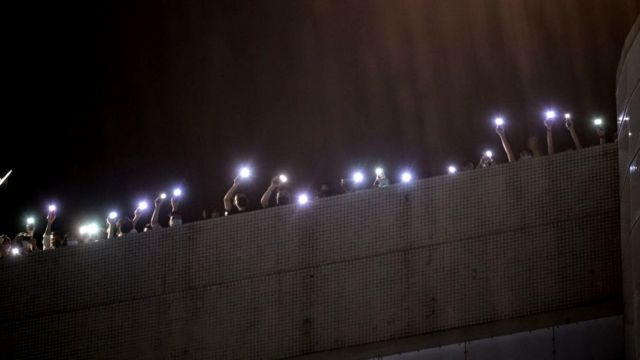 Employees of the Apple Daily newspaper shine phone torches from their office rooftop during heavy rain and shout thanks to supporters down