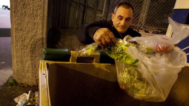Un hombre rebusca comida en un cubo de basura