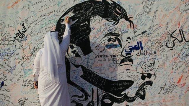 A man writes on a painting depicting Qatar's Emir Sheikh Tamim Bin Hamad Al-Thani in Doha, Qatar, 2 July 2017