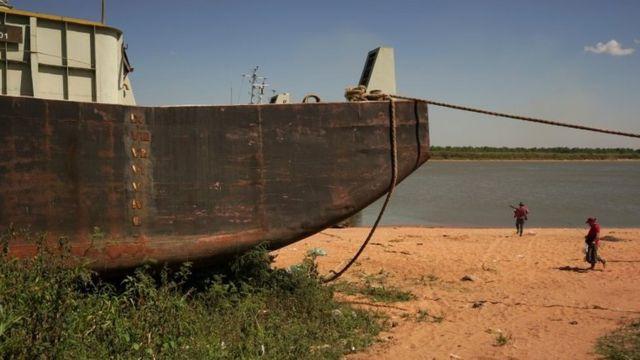Pessoas passam por uma barcaça encalhada na margem do Rio Paraguai, afluente do Paraná, pois a falta de chuvas no Brasil, onde o rio nasce, baixou o nível das águas, obrigando os navios de carga a reduzirem a quantidade de grãos que são carregados para exportação, em Ypane, Paraguai 30 de agosto de 2021