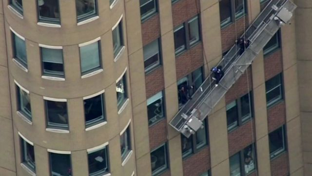 Window washers' scaffold dangles against building