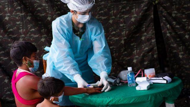 Com pano camuflado ao fundo, enfermeira prepara doses, ao lado de adulto e criança indígenas sentados - todos de máscara