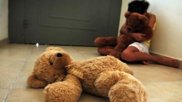 Foto ilustrativa sobre abuso infantil - criança abraça urso de pelúcia