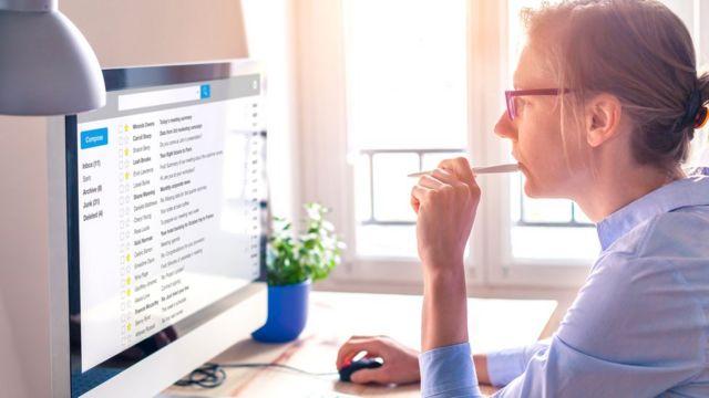 Женщина перед экраном компьютера, на котором - почтовый ящик электронной почты