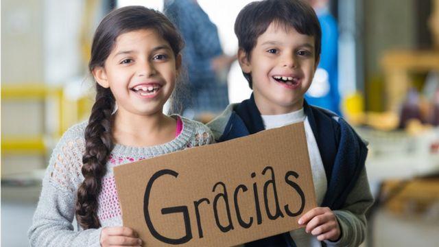 Una niña y un niño sostienen un letrero que dice Gracias.