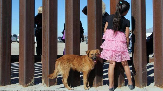 una niña en México mira a través de la frontera.