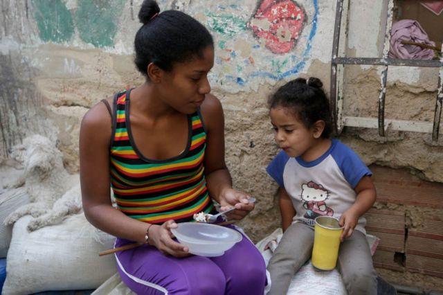 Una madre venezolana le da un poco de comida a su hija
