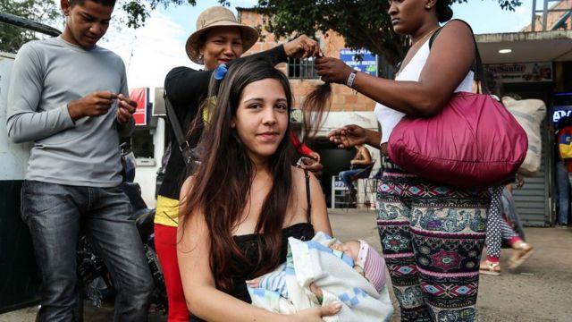 jovem corta o cabelo na fronteira da Venezuela com a Colômbia