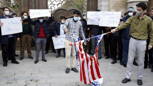 "Students wearing facemasks and holding signs saying ""Down with Israel"" and others in Farsi burn Israeli and US flags in Tehran at a protest outside Iran's foreign ministry in Tehran (28 November 2020)"