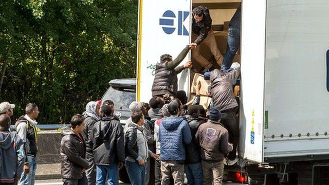 Migrants climb in the back of a lorry on the highway leading to the Eurotunnel