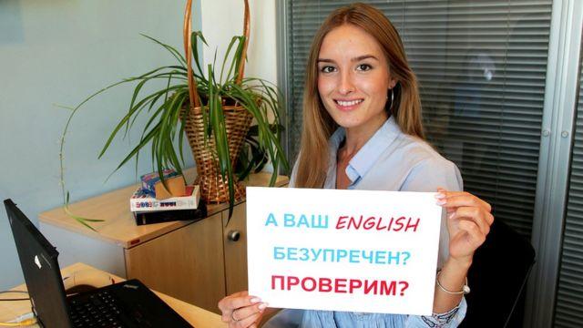 """Девушка с табличкой """"А ваш English безупречен? Проверим?"""" / Уроки английского языка, аудио, видео и тесты: как учить и проверять английский с Би-би-си"""