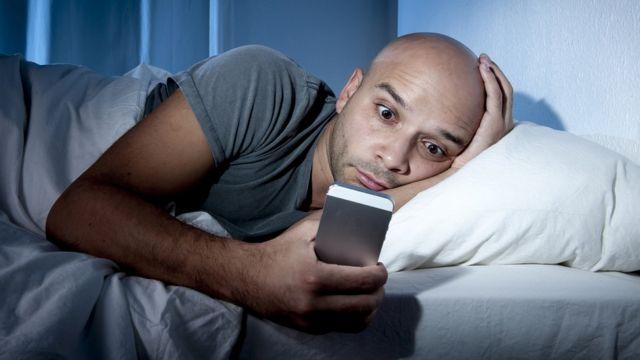 Hombre acostado en la cama revisando su celular
