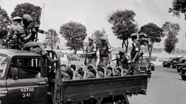 Para prajurit bersenjata mengangkut para terduga anggota Pemuda Rakyat, pada 10 Oktober 1965, dua hari sebelum diumumkannya penangkapan Letkol Untung.