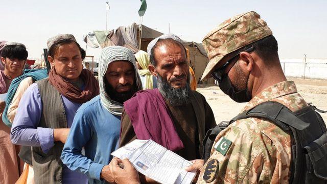 Un soldado pakistaní revisa los documentos de un migrante afgano