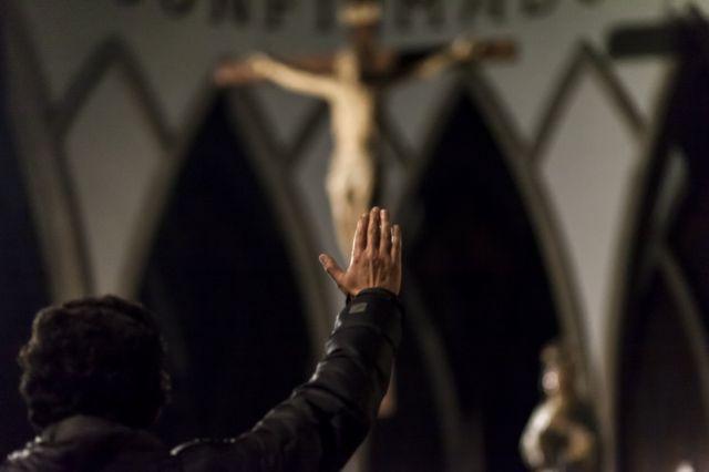 Hombre frente a Cristo levantando la mano