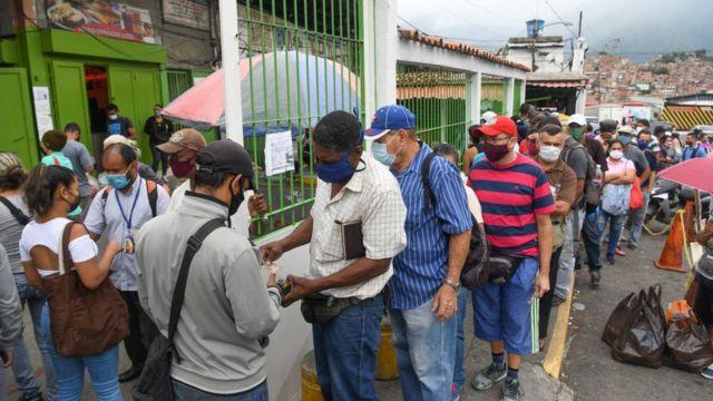 Venezolanos haciendo cola para comprar comida.