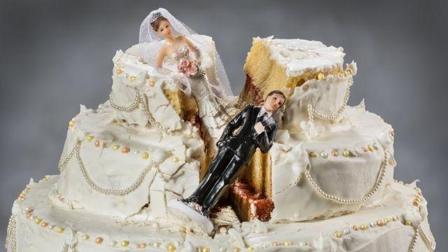 wedding cake with fallen figurines