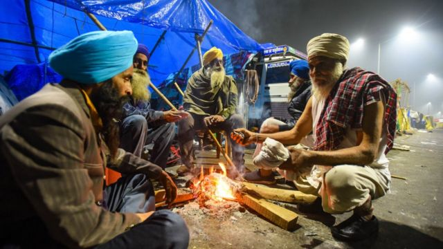 Farmer warm themselves around a bonfire at Ghazipur on January 28, 2021