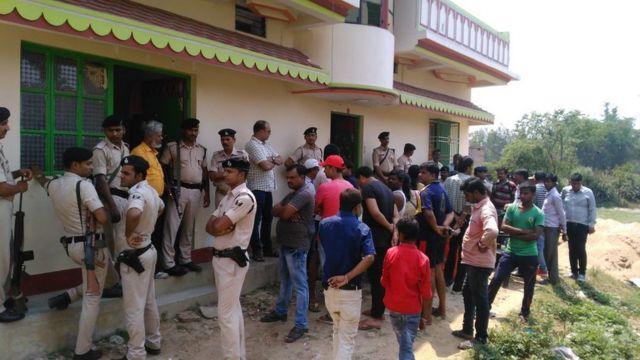 पीड़िता के घर के बाहर खड़े लोग और पुलिसकर्मी