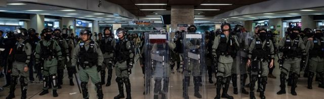 Hong Kong police line up at an MTR station on December 15