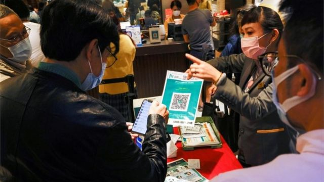 """A staff member holds a QR code for the """"LeaveHomeSafe"""" COVID-19 contact-tracing app to consumers at a restaurant, following the coronavirus disease (COVID-19) outbreak, in Hong Kong, China February 18, 2021"""