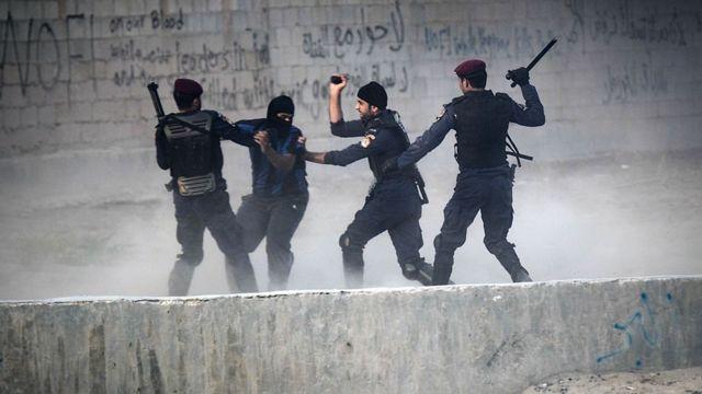 Bahraini police stop a demonstrator (File Photo)