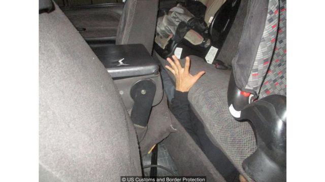 Una mano se asoma de la parte inferior del asiento trasero de un carro.