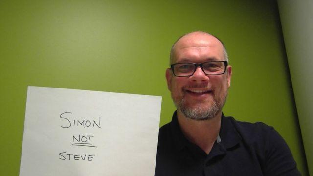 """Simon Hewett holds up a sign saying """"Simon not Steve"""""""