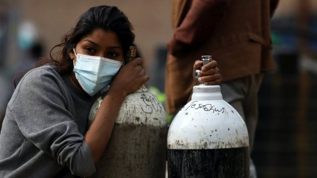 A woman holds on to the oxygen cylinders in Kathmandu, Nepal, 9 May 2021