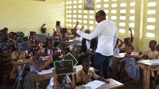 """MMoja wa wanamuziki wa bendi ya Ivory Coast """"Magic System"""" inayojumuisha mwanamuziki A""""Salfo (Kulia), akikutana na wanafunzi wa shule"""