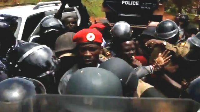 Bobi Wine (wambaye ingofero itukura) ubwo yatabwaga muri yombi na polisi ya Uganda