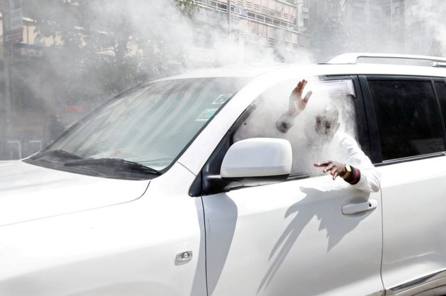 Caleb Amisi Luyai, an opposition politician, reacts after a gas canister fired by policemen hits his car.