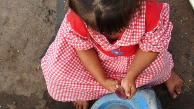 Una niña paraguaya lava unos cubiertos