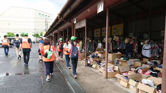 voluntários caminham pela rua de Soja