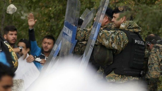 Macedonian riot police officers clash with migrants