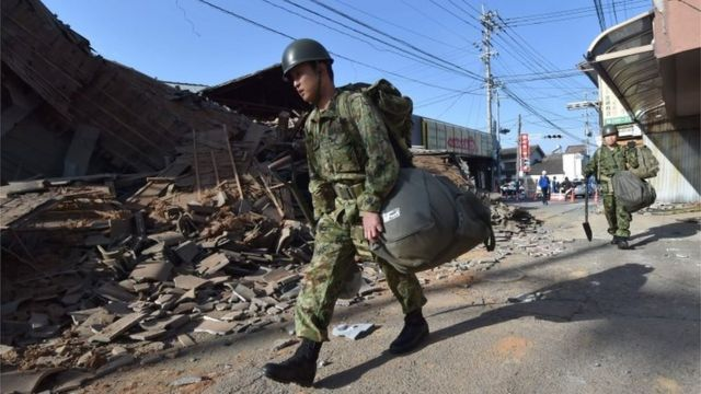 Members of Japan's self-defence forces walk past collapsed houses in Mashiki. Photo: 16 April 2016