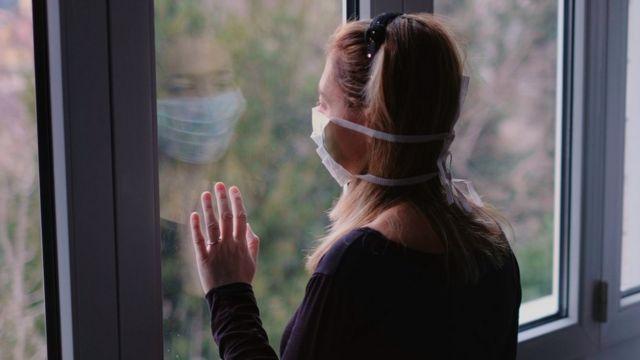 Una sola mujer con una mascarilla mira afuera por una ventana