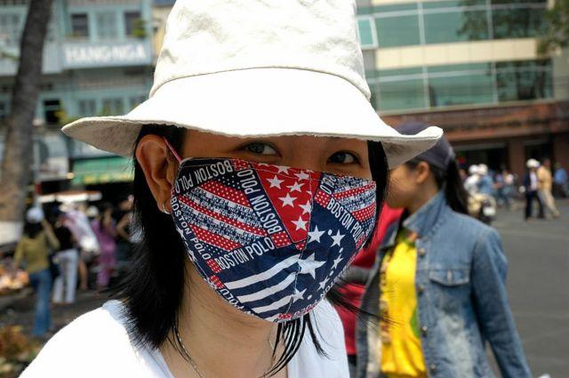 Một cô gái trên đường phố Việt Nam mang khẩu trang với những địa danh Mỹ