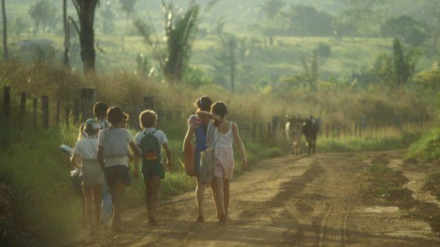 Crianças com uniformes e mochilas andam em estrada de terra em cena rural