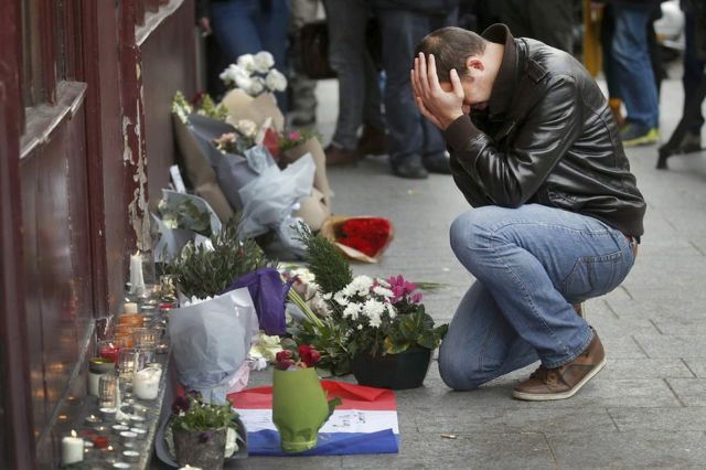 """Čovek odaje počast žrtvama ispred restorana """"Le Karilion"""", jutro posle napada u Parizu (14. novembar 2015)"""