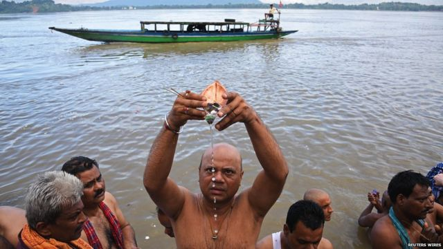 A Hindu man performs Tarpana, a religious ritual, on the banks of the river Brahmaputra to honour the souls of his departed ancestors during the auspicious day of Mahalaya in Guwahati.