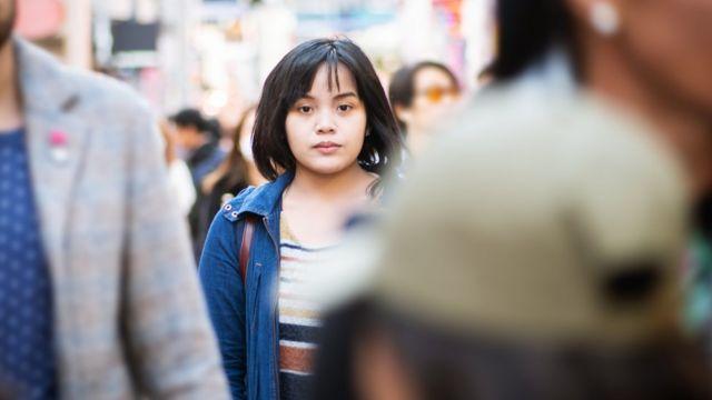 Une femme se promenant parmi les piétons dans une ville japonaise