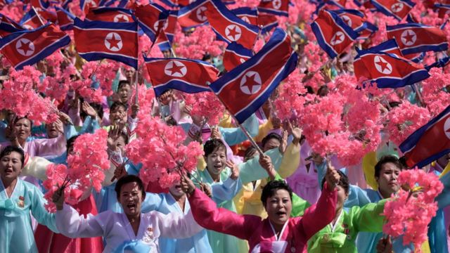 Participants wave flowers as they march past a balcony from where North Korea's leader Kim Jong Un was watching