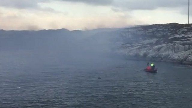 Boats and smoke near the site of helicopter crash off Bergen