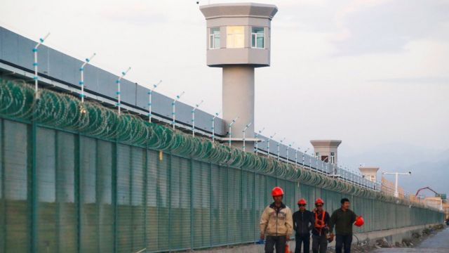 Workers walk by the perimeter fence of what is officially known as a vocational skills education centre in Dabancheng in Xinjiang Uighur Autonomous Region, China September 4, 2018.
