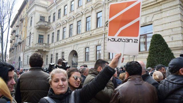 Женщина держит плакат