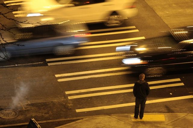 A man waits to cross the road as cars speed past him